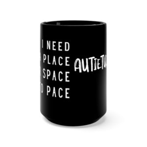 Black coffee mug with white print. On one side it says I NEED A PLACE FOR SPACE TO PACE. On the other side is the white AUTIETUDE logo.
