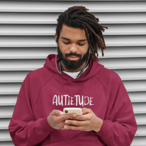 Bearded Black man standing outside while looking at his phone and wearing a red pullover-style hooded sweatshirt with kangaroo pocket. The white AUTIETUDE logo is printed across the chest.