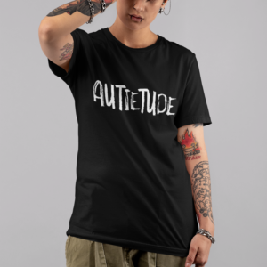 Androgynous, female presenting, tattooed person standing and posing for the camera with one hand on their head. They wearing a black t-shirt with a white AUTIETUDE logo across the chest.