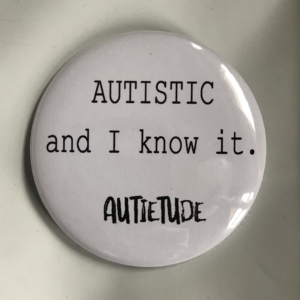 "2 and 1/4 inch round white pin with black print that says ""AUTISTIC and I know it."" followed by the black AUTIETUDE logo."
