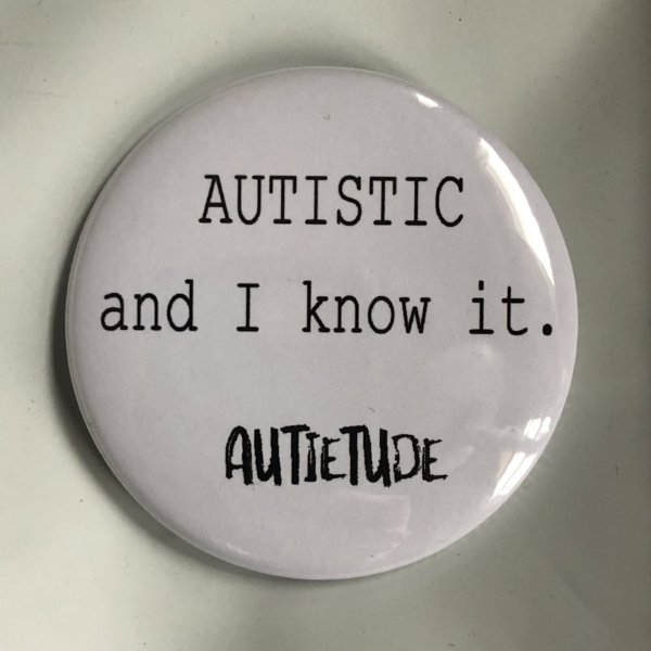 """2 and 1/4 inch round white pin with black print that says """"AUTISTIC and I know it."""" followed by the black AUTIETUDE logo."""