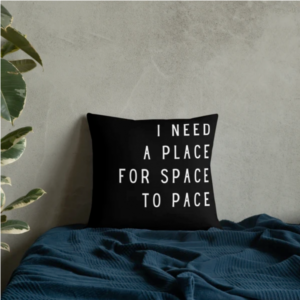 """A bed with a black throw pillow with white print that says """"I NEED A PLACE FOR SPACE TO PACE"""""""