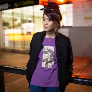 Asian woman, outside at night, standing near a storefront. She is leaning against a railing with her hands in her pockets and wearing an open black jacket. Under the jacket, she is wearing a purple t-shirt with a vertical block lettering design that says STIM followed by a white AUTIETUDE logo.