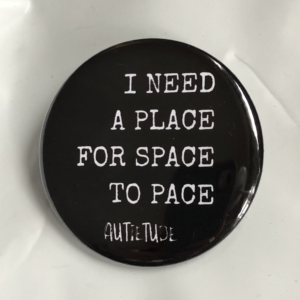 "2 1/4 inch round pin with a black background and white print that says ""I NEED A PLACE FOR SPACE TO PACE"" followed by the white AUTIETUDE logo."