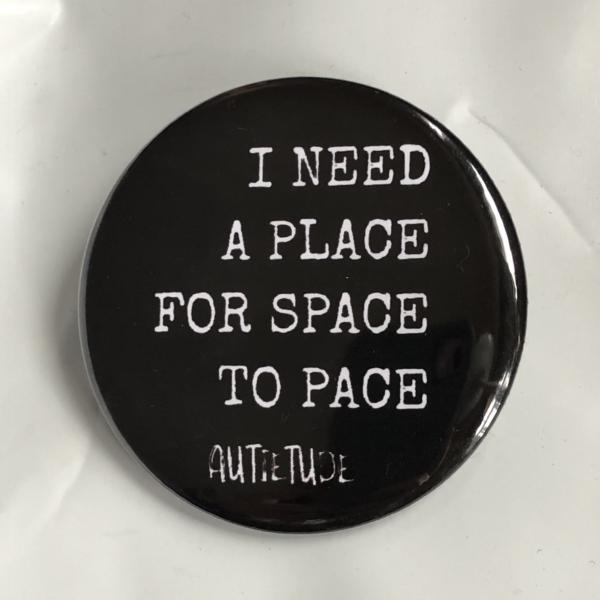 """2 1/4 inch round pin with a black background and white print that says """"I NEED A PLACE FOR SPACE TO PACE"""" followed by the white AUTIETUDE logo."""