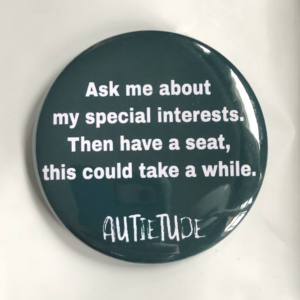 "2 1/4 inch pin with a green background and white print that says ""Aske me about my special interests. Then have a seat, this could take a while."" followed by the white AUTIETUDE logo."